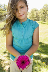 Young girl holding pink flower