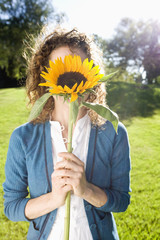 Woman holding sunflower in front of her face