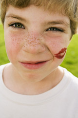 Grimacing boy with lipstick kiss on face