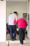 Hispanic man helping his grandmother to walk