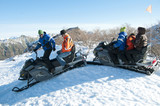 Hispanic family riding on snowmobiles through snow
