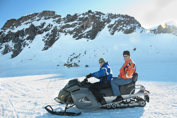 Hispanic men riding snowmobile together