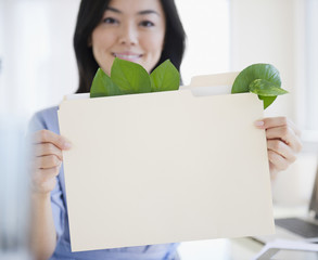 Japanese businesswoman holding folder containing leaves