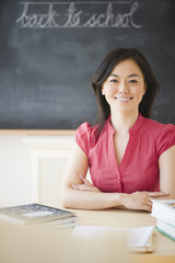 Japanese teacher sitting at desk in classroom