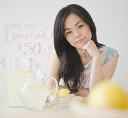 Frustrated Japanese woman sitting at lemonade stand