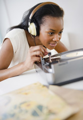 Black woman listening to record player