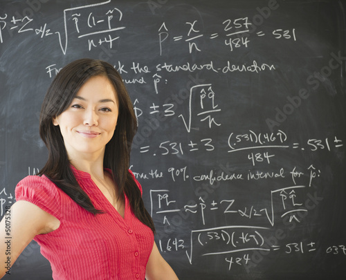 Japanese teacher standing near blackboard
