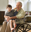 Caucasian man in wheelchair holding grandson on his lap