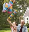 Caucasian man watching grandson hit piñata