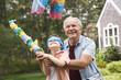 Caucasian man helping grandson hit piñata