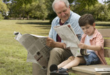 Caucasian grandfather and grandson reading newspapers in park