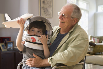 Caucasian boy in space helmet sitting on grandfather's lap