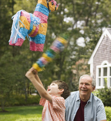 Caucasian man watching grandson hit piñata