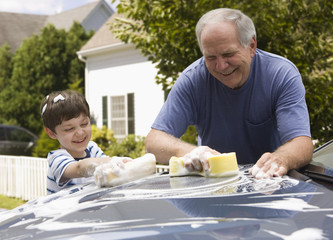 Caucasian man and grandson washing car