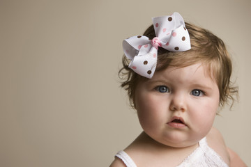 Cute Caucasian baby girl with bow in her hair