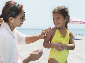 Hispanic mother putting sunscreen on daughter at beach
