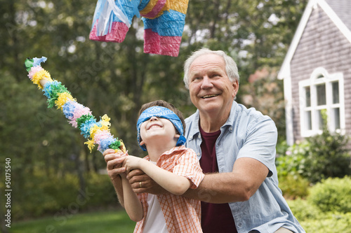 Caucasian man helping grandson hit piñata