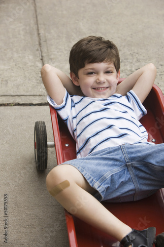 Caucasian boy laying in wagon