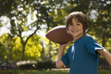 Caucasian boy throwing football