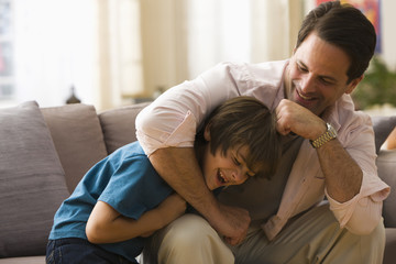 Caucasian father rough housing with son in living room