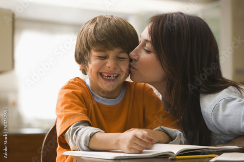 Caucasian mother kissing son