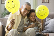 Grandfather and grandson holding balloons with smiley faces