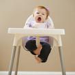 Caucasian baby girl yawning in high chair