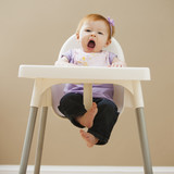 Caucasian baby girl yawning in high chair