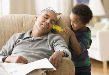 Grandson teasing sleeping grandfather
