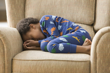 Black boy sleeping in armchair