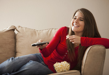 Caucasian woman watching television and eating popcorn