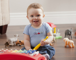 Caucasian baby boy playing with xylophone