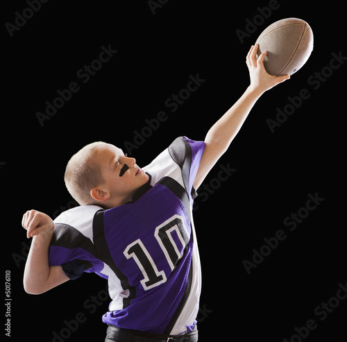 Caucasian football player holding up football