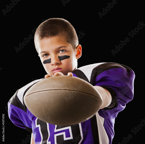 Mixed race football player holding football