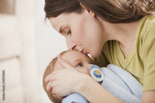 Caucasian mother kissing baby boy
