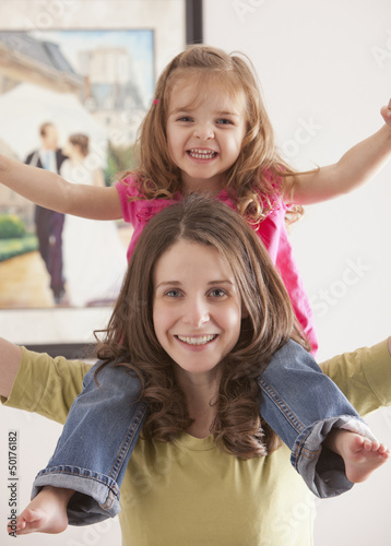 Caucasian mother carrying daughter on her shoulders