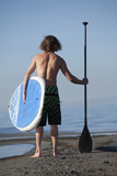 Caucasian man standing on beach with paddle board