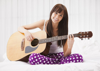 Caucasian woman playing guitar on bed