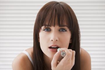 Caucasian woman applying lipstick