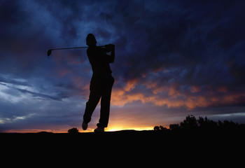 Caucasian golfer swinging golf club at sunset
