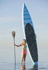 Caucasian woman standing in water with paddle board