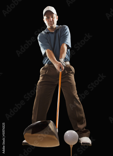 Caucasian golfer about to hit golf ball