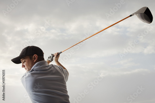 Caucasian golfer swinging golf club