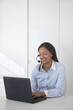Black businesswoman using laptop and talking on headset