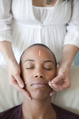 Black woman receiving acupuncture treatments
