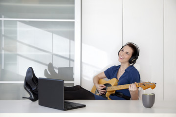 Caucasian businesswoman playing guitar at desk