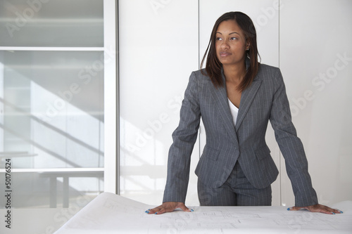 Black architect reviewing blueprints in office
