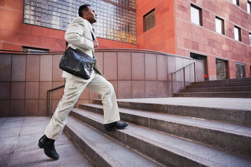 African American businessman running up steps