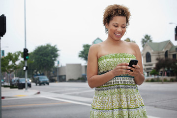 African American woman text messaging on cell phone