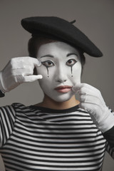 Woman in mime costume stretching her face